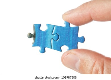 United two puzzle in the fingers. On a white background.