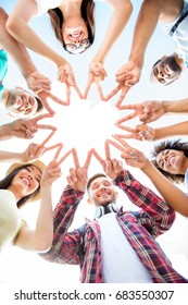 Unity and connection of people. Topview of multi ethnic students friends, putting their fingers together, wearing casual clothes, otdoors on a sunny day. Conception of successful teambuilding