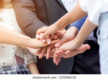 Unity and teamwork concept; Close up top view of business people putting their hands together. Stack of hands.