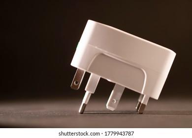 universal electric socket plug adapters, isolated on black background.