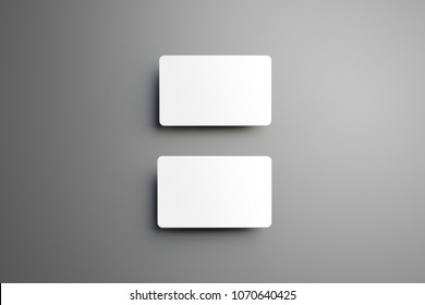 Universal mockup of a two  bank (gift) cards placed vertically with shadows on a gray background. Top of view.