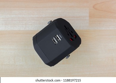 Universal Power Adapter, plug for travel with dual USB ports. All in one travel adaptor in black on wooden background