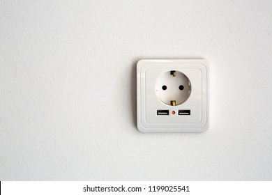 universal power socket European standard 220 volt with two connectors usb for charging mobile devices. socket white plastic on a white wall with copy space for text.
