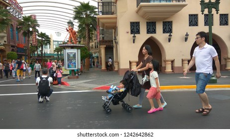 Universal Studios/ Singapore- April 30, 2016: Tourists from various parts of the world roam around the park. An Asian family with a baby in trolley is seen.