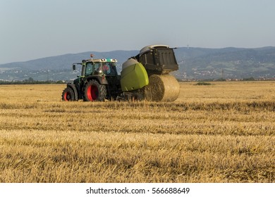 Universal tractor harvesting straw in the field. Baling machine.