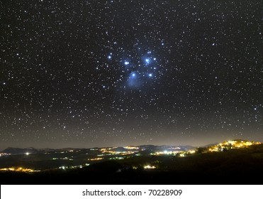 The Universe above city lights. The Pleiades star cluster.