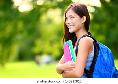 University / college student girl looking happy smiling with book or notebook in campus park. Beautiful young mixed race Asian Chinese / Caucasian young woman female model.