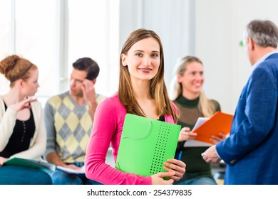 University college student standing in class room with professor
