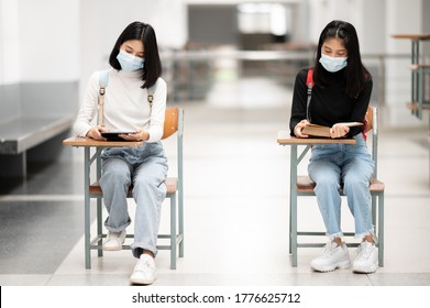 Universitätsstudenten sitzen im Raum der sozialen Distanzierung, um übertragbare Krankheiten zu verhindern.