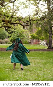 University graduate on her college campus in a cap and gown celebrating graduating from her undergrad bachelor's degree during the Spring.