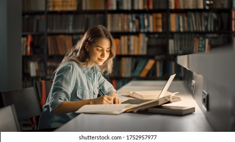 University Library: Beautiful Smart Caucasian Girl uses Laptop, Writes Notes for Paper, Essay, Study for Class Assignment. Focused Students Learning, Studying for College Exams. Side View Portrait