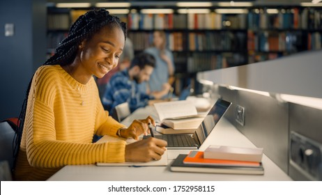 University Library: Gifted Black Girl uses Laptop, Writes Notes for the Paper, Essay, Study for Class Assignment. Diverse Multi-Ethnic Group of Students Learning, Studying for Exams, Talk in College