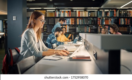 University Library: Talented Caucasian Girl Sitting at the Desk, Uses Laptop, Writes Notes for the Paper, Essay, Study for Class Assignment. Diverse Group of Students Learning, Studying for Exams.