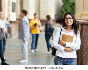 University life. Happy asian girl holding books and smiling, resting between classes