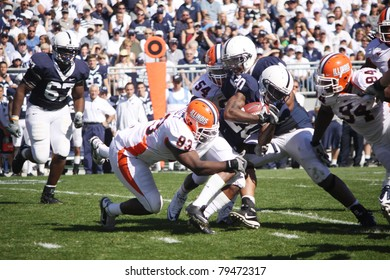 UNIVERSITY PARK, PA - OCT 9: Penn State's #20 Devon Smith is tackled by several Illinois players at Beaver Stadium October 9, 2010 in University Park, PA