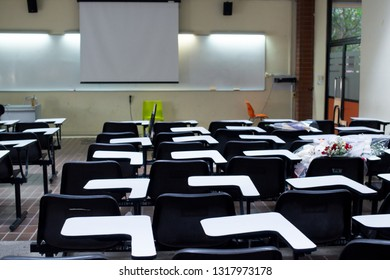 University or school black lecture chairs and white tables in classroom.