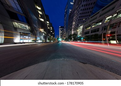 University Street in Montreal with silhouette cars with red rear light and traffic light, with offices buildings background, at dusk. (8mm Circular Fish eye Effect)