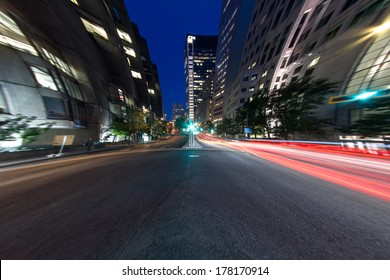 University Street in Montreal with silhouette cars with red rear light and traffic light, with offices buildings background, at dusk (4.5 mm Circular Fish eye Effect)