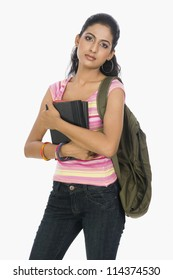A university student carrying a bag and books
