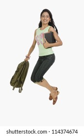University student jumping with bag and books