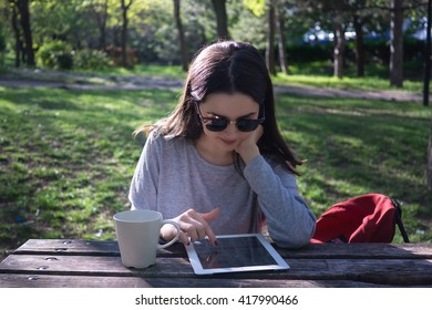 University student with sunglasses using digital tablet in park