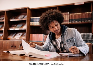 University student taking notes from book while sitting in the library. Young black man writing notes in library.