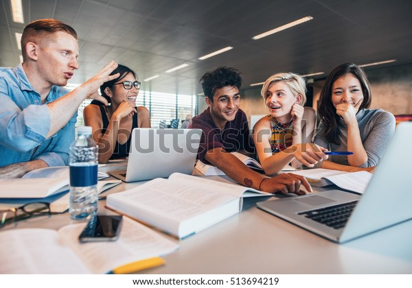 University students using laptop in a library. Students working together on academic project finding information on internet.