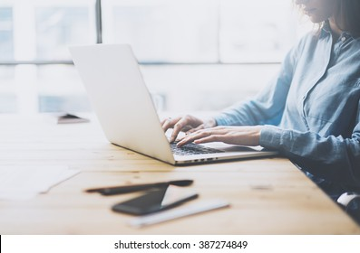 University work process concept. Student girl working new project with generic design laptop.  Smartphone wooden table, texting message. Blurred background, film effect. Horizontal