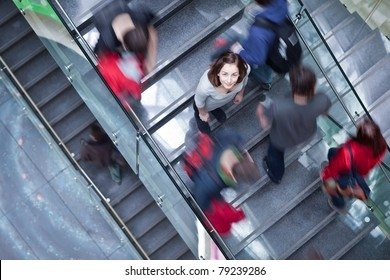 At the university/college - Students rushing up and down a busy stairway - confident pretty young female student looking upwards (color toned image)