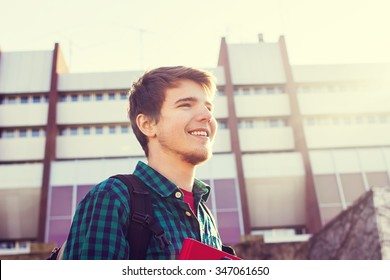 University.Smiling young student man holding a book and a bag on a university background .Young smiling student  outdoors Life style.City.Student.