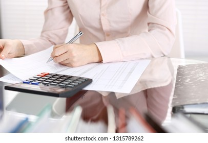 Unknown bookkeeper woman or financial inspector  making report, calculating or checking balance, close-up. Business portrait. Audit or tax concepts