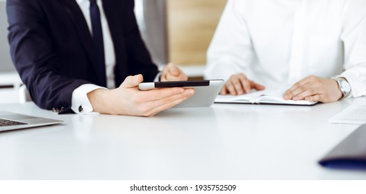 Unknown business people using tablet computer in modern office. Businessman or male entrepreneur is working with his colleague at the desk
