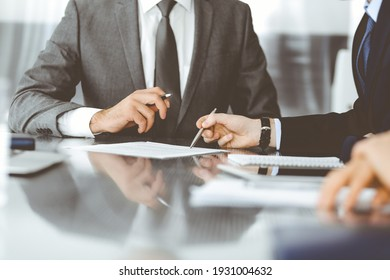Unknown business people working together at meeting in modern office, close-up. Businessman and woman with colleagues or lawyers discussing contract at negotiation