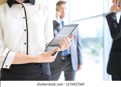 Unknown business woman using tablet computer in office hall among businesspeople