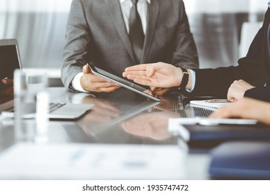 Unknown businessman using tablet computer and working together with his colleague while sits at the glass desk in modern office. Teamwork and partnership concept