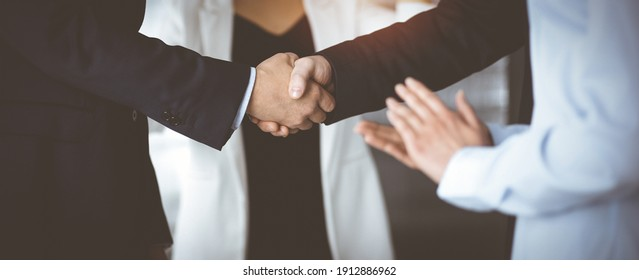 Unknown businesspeople are shaking their hands after signing a contract, while standing together in a sunny modern office, close-up. Business communication, handshake, and marketing concept