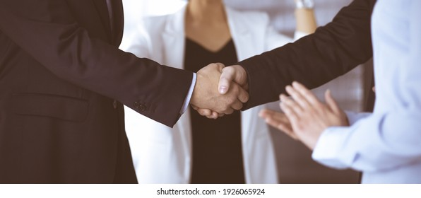 Unknown businesspeople are shaking their hands after signing a contract at meeting, close-up. Business communication concept - Shutterstock ID 1926065924