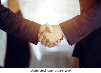 Unknown businesspeople are shaking their hands after signing a contract, while standing together in a sunny modern office, close-up. Business communication concept - Shutterstock ID 1935441949
