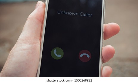 Unknown caller. A woman holds a phone in his hand outdoors in a park and thinks to end the call. Incoming from an unknown number. Incognito or anonymous