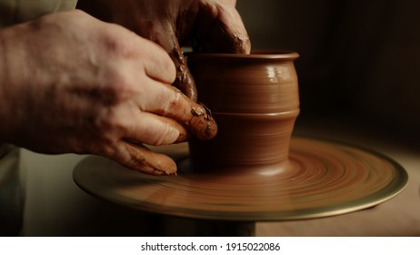 Unknown clay artist forming jar from wet clay piece in workshop. Unrecognized master modeling product in studio on potters wheel. Closeup man hands sculpting in pottery.