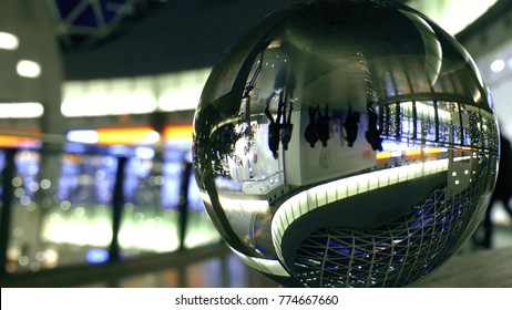 Unknown customers walk in a modern shopping mall. Distorted view through the glass sphere