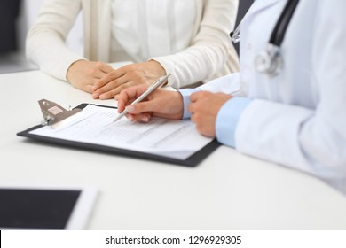 Unknown doctor and  female patient  discussing something while standing near reception desk in emergency hospital. Physician at work in clinic. Medicine and health care concept