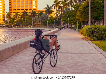 An Unknown Elderly Man Riding a recumbent bicycle With Helmet in a tropical clean urban location next to the water. Aged Fitness Man Maintaining a Healthy Lifestyle