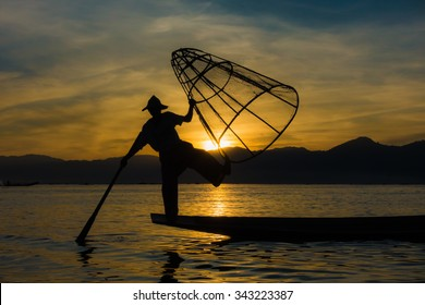 An unknown fishermen at Myanmar's Inle Lake strikes a pose in front of the sun