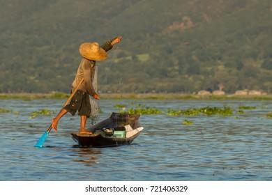 An unknown fishermen at Myanmar's Inle Lake keeping balance while fishing and leg rowing