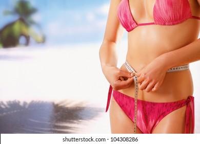 Unknown girl in bikini with tape-measure at sea