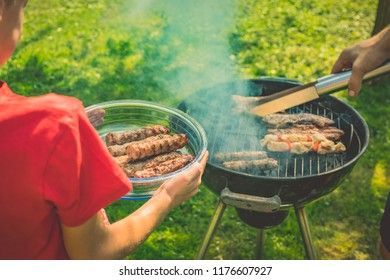 Unknown kid in a red shirt is recieving meat from a grill while holding a glass plate or bowl with ready meat. Round grill in smoke with cevapcici on it on a garden lawn