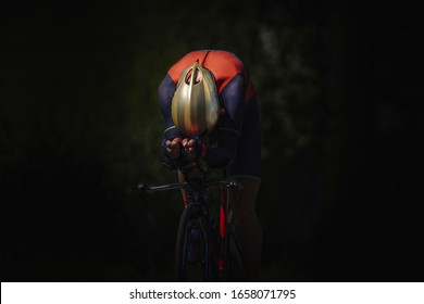 Unknown male cyclist riding on aerodynamic mode in the dark. He is using a time trial bike. He is wearing gold helmet and red and blue cycling gear. He is alone.