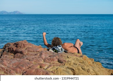unknown man enjoying the sun on a rock at St. Tropez, France