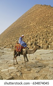 Unknown man with his camel in front of a pyramid in Giza, Cairo, Egypt. Picture taken in september 2016 in Giza, Egypt